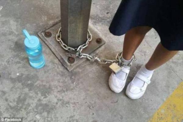 صورة - عاقبت ابنتها بربط قدمها بعمود في موقف للسيارات لأنها رفضت الذهاب للمدرسة