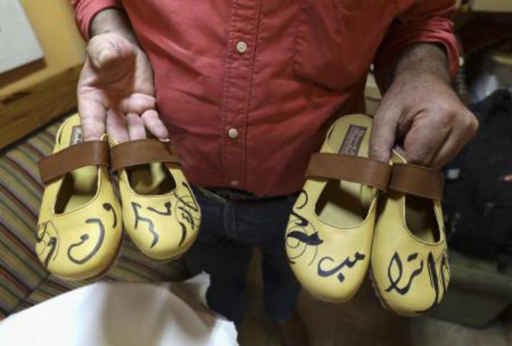 فلسطيني يختم بالخط العربي اسمي ترامب وماكرون على أحذية يصنعها يدويا (صور)